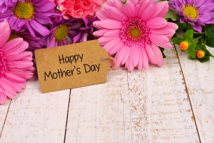 Happy Mothers Day tag close up with flowers over white wood